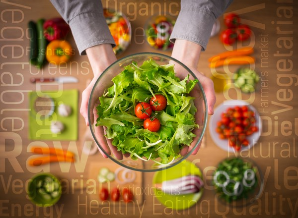Hands holding an healthy fresh vegetarian salad in a bowl fresh raw vegetables on background and healthy eating text concepts
