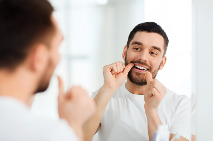 man with dental floss cleaning teeth at bathroom