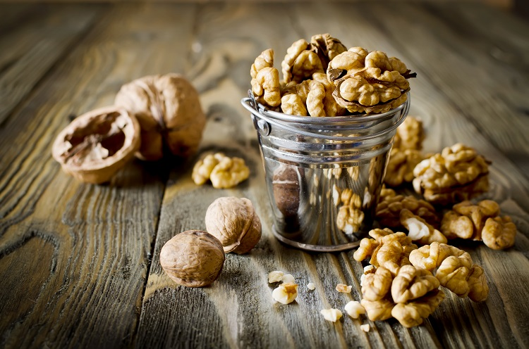 Walnut kernels and whole walnuts on wooden table. Selective Focus